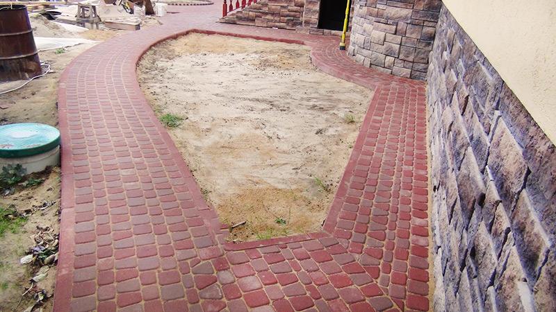 Укладка тротуарной плитки начинается от стен фундамента методом от себя